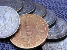 Bitcoin and a row Silver Morgan Dollars. Closeup of Bitcoin on a line of a few Silver Morgan Dollars on Black Background stock photos