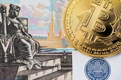 Bitcoin with Russian ruble banknote. Golden Bitcoin cryptocurrency on Russian Rubles banknotes. New virtual money concept. One Bitcoin on Russian banknotes stock photos