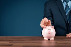 Bitcoin savings and investment. Concept. Businessman insert bitcoin coin in piggy bank royalty free stock photography
