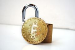 Bitcoin security concept. Gold coin with padlock royalty free stock image