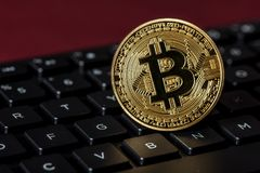 Close up of a Bitcoin replica near the letter B on a keyboard Stock Photos
