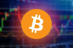 Bitcoin sign over blurry financial stock market graph chart of stock market investment trading screen.  Royalty Free Stock Photos