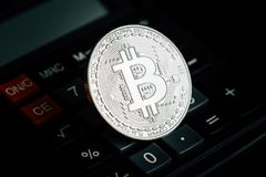 Bitcoin silver coin on calculator keyboard. Virtual cryptocurrency concept royalty free stock image