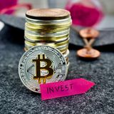 Bitcoin silver coin and pink invest arrow. Digital currency physical silver bitcoin coin and pink invest arrow Stock Photos