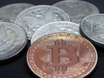 Bitcoin on Silver Morgan Dollars. Closeup of Bitcoin and pile of Silver Morgan Dollars on Black Background royalty free stock photos