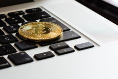 Bitcoin sobre un teclado del ` s del ordenador portátil foto de archivo libre de regalías
