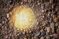 Bitcoin som är guld- på jordjord som är djup med ljus faktisk cryptocurrencybitcoin som bryter begrepp arkivfoto