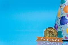Bitcoin som firar 10 år årsdag, myntet med födelsedaghatten bak den och 10 år undertecknar, med blått kopieringsutrymme royaltyfria foton