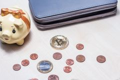 Bitcoin, euros, wallet and a piggy bank. Bitcoin, some euro coins, wallet and a small yellow piggy bank Stock Image