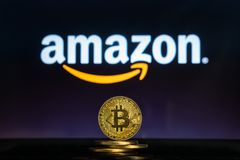 Amazon logo on a computer screen with a stack of Bitcoin cryptocurency coins. royalty free stock images