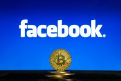 Facebook logo on a computer screen with a stack of Bitcoin cryptocurency coins. royalty free stock photos