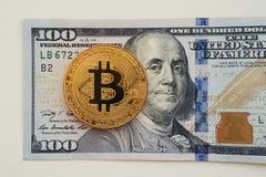 Bitcoin sur le fond de billet d'un dollar 100 pièce d'or de bitcoin sur cent billets d'un dollar Photos libres de droits