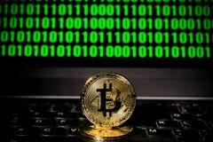 Bitcoin sur un ordinateur portable avec l'écran du code binaire Photos stock