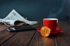 Bitcoin-Symbol mit Morgen Tasse Kaffee, Zeitung und Smartphone lizenzfreie stockfotografie