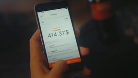 Bitcoin symbol på mobilapp-skärmen med stora KÖP- och FÖRSÄLJNINGSknappar materiel Bitcoin på aktiemarknad Man som använder mobil royaltyfria bilder