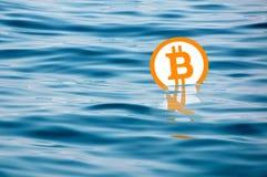 Bitcoin symbol swimming in the sea. royalty free stock photo