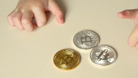 The bitcoin is on the table, and the baby`s hand touches the bitocoins. The future is the crypto currency. Slow motion stock footage