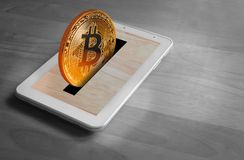 Bitcoin tablet moneybox. Photo of a gold bitcoin cryptocurrency digital coin being deposited in a tablet moneybox Stock Images