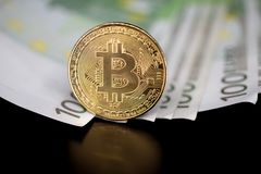 Bitcoin token on black with reflection, on top of 100 euro banknotes money. royalty free stock photography