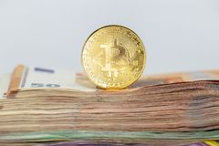 Bitcoin token on white background, on top of many euro banknotes money stock image