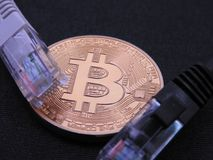 Bitcoin with on top two rj-45 plugs Royalty Free Stock Photos
