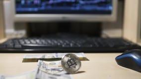 Bitcoin tourne et de billets d'un dollar tombant près de l'ordinateur clips vidéos