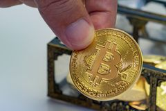 Bitcoin Treasure Chest. Close up of a hand picking out a Bitcoin coin from a treasure chest Stock Photography