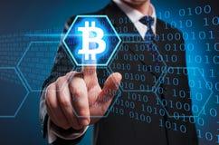 Bitcoin Un uomo in un vestito ed in un legame clicca il dito indice sul Immagine Stock