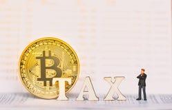 Bitcoin und Holzklötze mit STEUER-Buchstaben lizenzfreies stockfoto