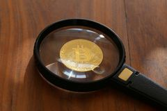 Bitcoin under the magnifying glass. Bitcoin. Physical bit coin. Digital currency. Cryptocurrency Royalty Free Stock Images