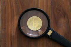 Bitcoin under the magnifying glass. Bitcoin. Physical bit coin. Digital currency. Cryptocurrency Stock Photo