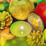 Bitcoin unter Weihnachtsdekorationen und einer Kerze Lizenzfreies Stockbild
