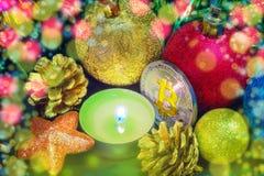 Bitcoin unter Weihnachtsdekorationen und einer Kerze Lizenzfreies Stockfoto