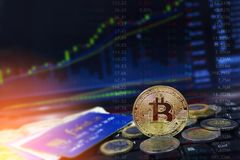 Bitcoin valuta med kreditkortar och mynt på bärbar datortangentbordet med stigande pris kartlägger i bakgrunden arkivfoto