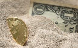 Bitcoin valuta som ses som begravas delvist i silikonsand samman med en en dollar sedel Royaltyfria Bilder