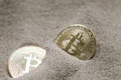 Bitcoin valuta som ses som begravas delvist i silikonsand samman med en en dollar sedel Royaltyfri Bild