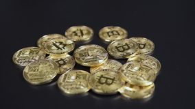 Bitcoins virtual currency pile. Bitcoin virtual currency dropping on the black background stock video footage
