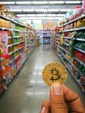 Bitcoin, Virtual Digital money coin. And Abstract blur shopping mall of luxury department store background. Virtual money with trading in the real world concept Stock Photos