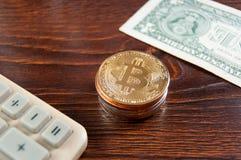 Bitcoin virtuale dei soldi e un calcolatore con i dollari per contare i profitti fotografie stock