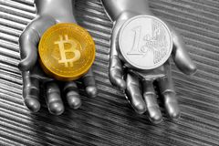 Bitcoin vs euro coins concept on silver futuristic. Hands Royalty Free Stock Image