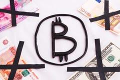 Bitcoin wird vom Plastik gemacht, der durch gekreuzte heraus Banknoten von verschiedenen Ländern umgeben wird Einzigartig und Aus Stockfoto