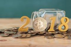 Bitcoin y año de madera 2018 del texto en la pila de las monedas, cryptocurrency Imagenes de archivo