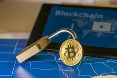 Bitcoin y abre el candado sobre un mapa de los E.E.U.U. y una pantalla con palabra del blockchain Foto de archivo libre de regalías