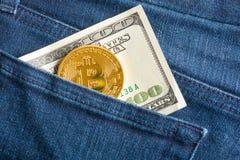 Bitcoin y billete de dólar 100 en un bolsillo Foto de archivo