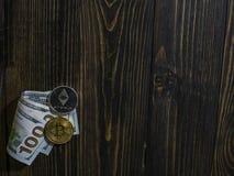 Bitcoin y Ethereum en los billetes de banco de cientos d?lares en un fondo de madera Imagen conceptual para el cryptocurrency mun imágenes de archivo libres de regalías
