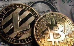 Bitcoin y Litecoin sobre billetes de banco del dólar Fotografía de archivo libre de regalías