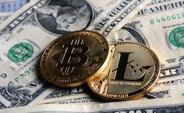 Bitcoin y Litecoin sobre billetes de banco del dólar Imagenes de archivo