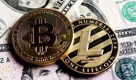 Bitcoin y Litecoin sobre billetes de banco del dólar Imagen de archivo libre de regalías
