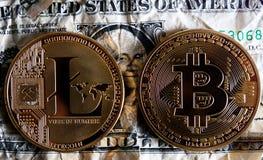 Bitcoin y Litecoin sobre billetes de banco del dólar Fotos de archivo libres de regalías
