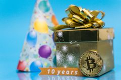 Bitcoin 10 year anniversary, coin with birthday golden present and birthday hat behind it and 10 years sign, copy space. Closeup photo of Bitcoin cryptocurrency royalty free stock photos
